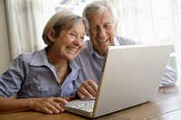 Germany, Bavaria, Senior couple using laptop at home, smiling