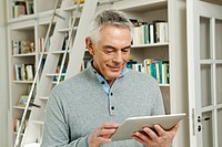 Germany, Berlin, Senior man using tablet pc, smiling