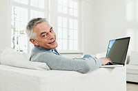 Germany, Berlin, Senior man using laptop, portrait