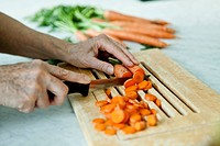 Germany, Berlin, Senior man cutting carrots (thumbnail)