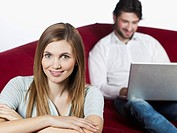 Woman smiling, man using laptop in background