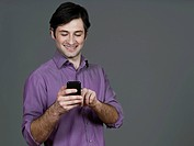 Young man using mobile phone, smiling