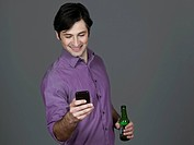 Young man with beer bottle and mobile phone, smiling