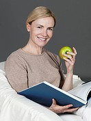 Mature woman with book and apple, smiling, portrait