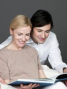 Man and woman reading book, smiling