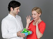 Man giving gift to woman, smiling