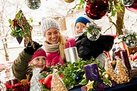 Austria, Salzburg, Mother with children at christmas market, smiling