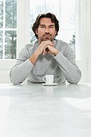 Germany, Berlin, Mature man with coffee cup, portrait