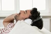 Germany, Berlin, Mature man listening music with head phones