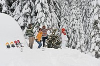 Austria, Salzburg, Men and women dancing by christmas tree in winter (thumbnail)