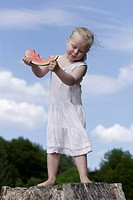 Germany, Bavaria, Girl standing eating piece of watermelon
