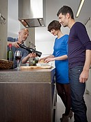 Germany, Cologne, Men and woman cooking together in kitchen