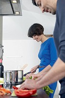 Germany, Cologne, Man and woman cooking together in kitchen (thumbnail)