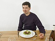 Germany, Cologne, Mid adult man having dinner in kitchen, smiling, portrait