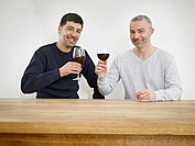 Germany, Cologne, Men drinking wine in kitchen, smiling, portrait