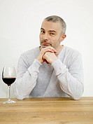Germany, Cologne, Mature man with wine in kitchen, portrait