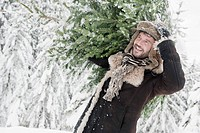 Austria, Salzburg County, Mature man carrying christmas tree, smiling