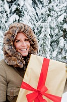 Austria, Salzburg County, Mid adult woman standing with christmas parcel, smiling, portrait