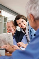 Germany, Leipzig, Senior man reading newspaper, man and woman smiling