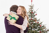 Couple embracing with gift in hand, smiling