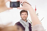 Woman taking photograph of mid adult man, smiling
