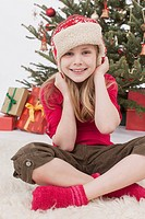 Girl with Santa hat sitting on carpet, smiling, portrait