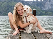 Austria, Teenage girl with dog on jetty, smiling, portrait