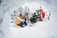 Austria, Salzburg, Men and women sitting at fire place in winter