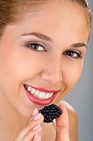 Woman eating blueberry.