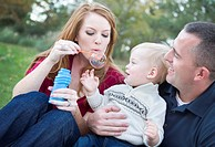 Young Parents Blowing Bubbles with their Child Boy