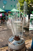 Youngsters cool off with water sprayed from a properly capped fire hydrant during the opening of the Summer Play Streets program in a Police Athletic ...