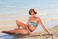 Young dark_skinned woman posing in a bikini on the beach