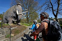 Cyclists on electric bicycles in front of a mammoth sculpture near Siegsdorf, Chiemgau region, Upper Bavaria, Bavaria, Germany, Europe