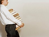 Businessman Carrying Stack of Books