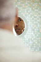 Man Inspecting Face in Mirror