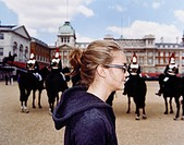 Young woman next to Guards on horses, Buckingham Palace, London, England