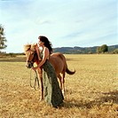 Woman Standing with Horse in Field