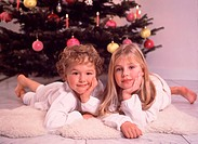 Two children next to Christmas tree