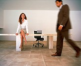 Businessman Walking Past Businesswoman in Office