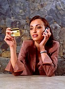 Young Woman Holding Credit Card Using Cell Phone