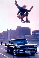 Male inline skater jumping over vintage car