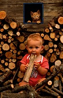 Little child sitting between wood