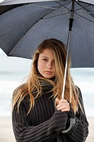 teenager holding umbrella under the rain