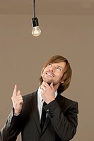 Businessman wearing suit looking at light bulb