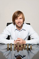 Smiling man at desk with stacks of coins