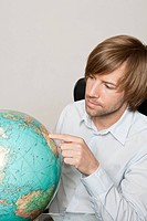 Man pointing finger on globe