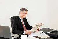 Smiling manager reading newspaper at desk