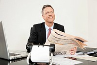 Smiling manager with newspaper at desk looking up