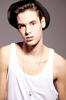 Young man wearing hat and undershirt