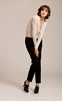 Brunette woman wearing beige top and black pleated pants